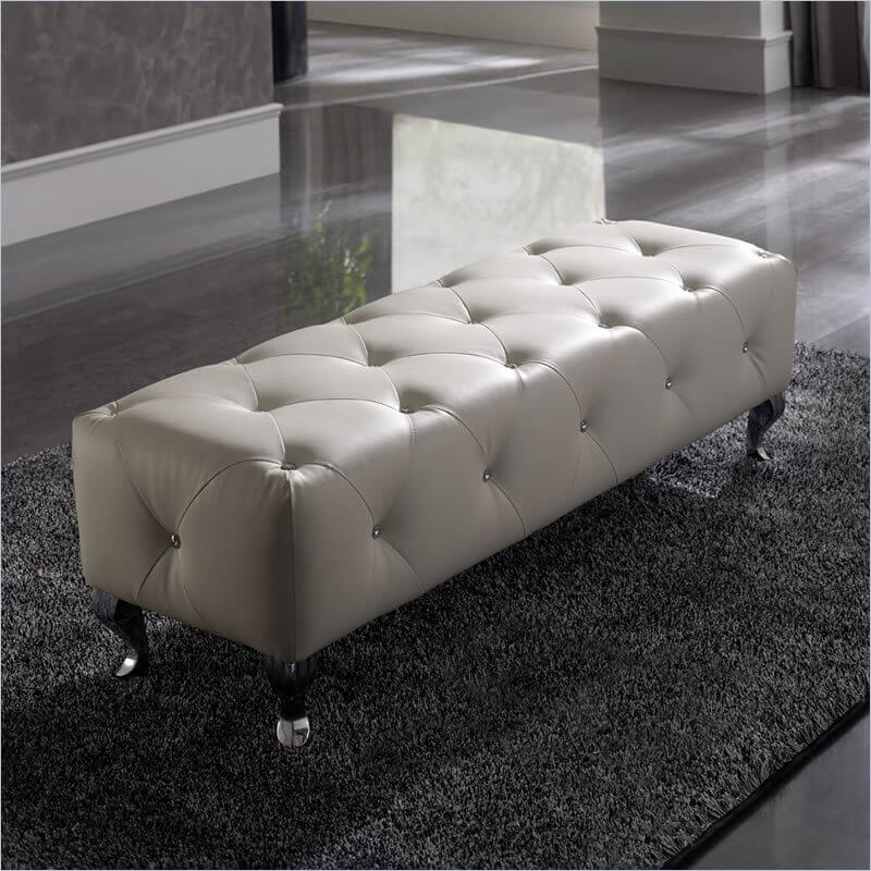 A low tufted ottoman with crystal buttons and elegant curved legs. Perfect as an ottoman or as a bench in a walk-in closet or at the foot of a bed.