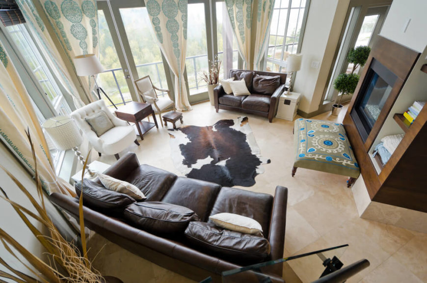 An above view of a contemporary living room with a cowhide rug. This living room has three end tables; one dark wood, two white. Each table sits next to a different seating arrangement. The two white tables sit on one side of the sofa and love seat and are topped by modern lamps in chrome. The single dark wood end table is of a more traditional design, and serves as a barrier between the two chairs to the rear of the room. Behind it is a floor lamp.