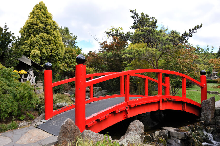 The pattern of the stone walkway gives way to a sturdy tread over wooden planks. The bold red railings are topped with glossy black balls.