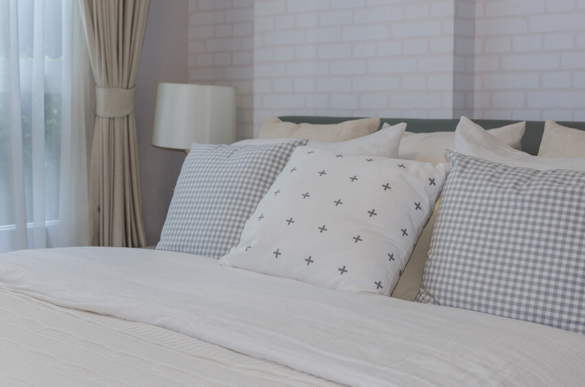Simple square throw pillows in varying patterns make a big impact against the white brick wall and ivory linens.