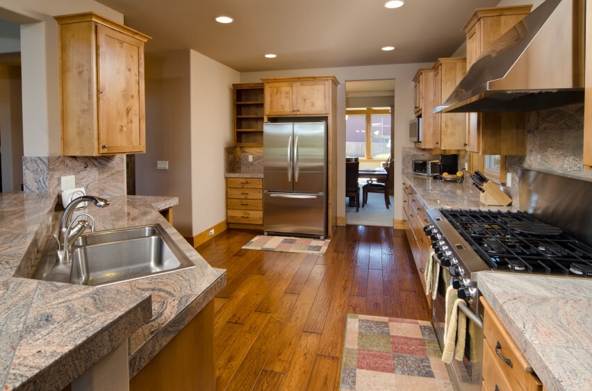 The golden color of these natural wood floors warms up the tone of the cabinets and accentuates the swirling texture of the countertops and backsplash.