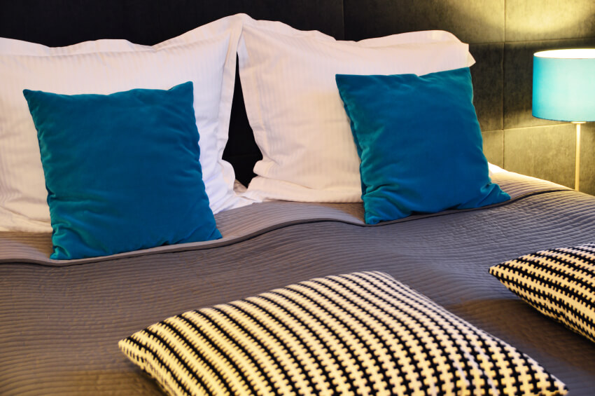Stone tiled walls overlook a simple accent pillow arrangement featuring soft turquoise blues and black and white patterned square accents.