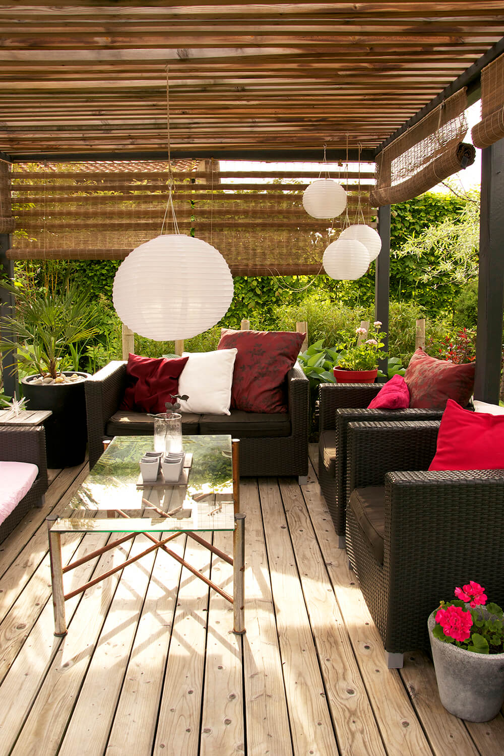 This deck offers lovely seats and throw pillows along with classy pendant lights.