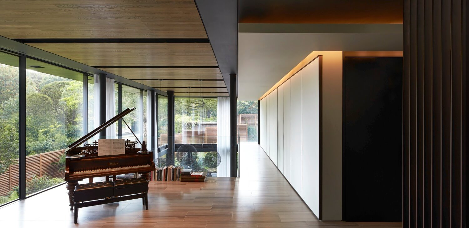 """The upper floor continues into this minimalist """"study"""" space, with a small library of books leaning against the glass railing behind a grand piano. The panoramic views afforded on this floor are unrivaled."""