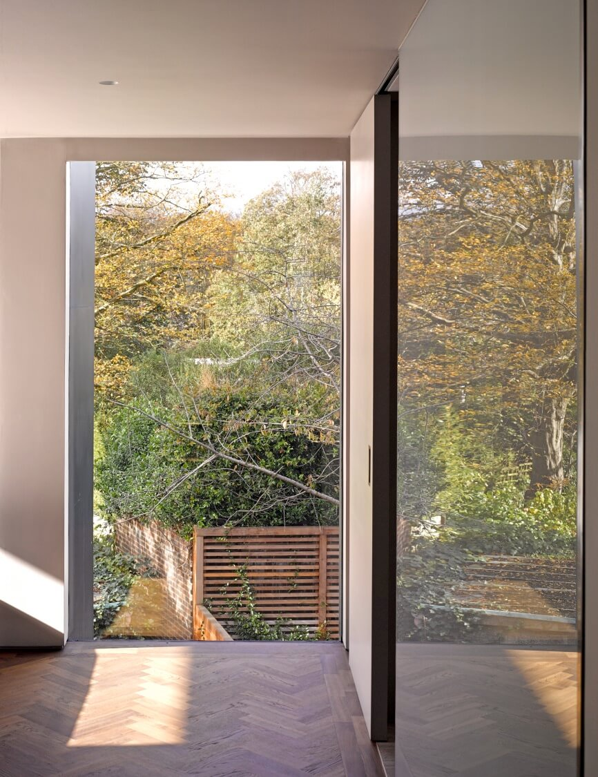 Looking down through the full height glazing, the surrounding greenery wraps the home in a private space while the glass helps erase boundaries between indoor and out.