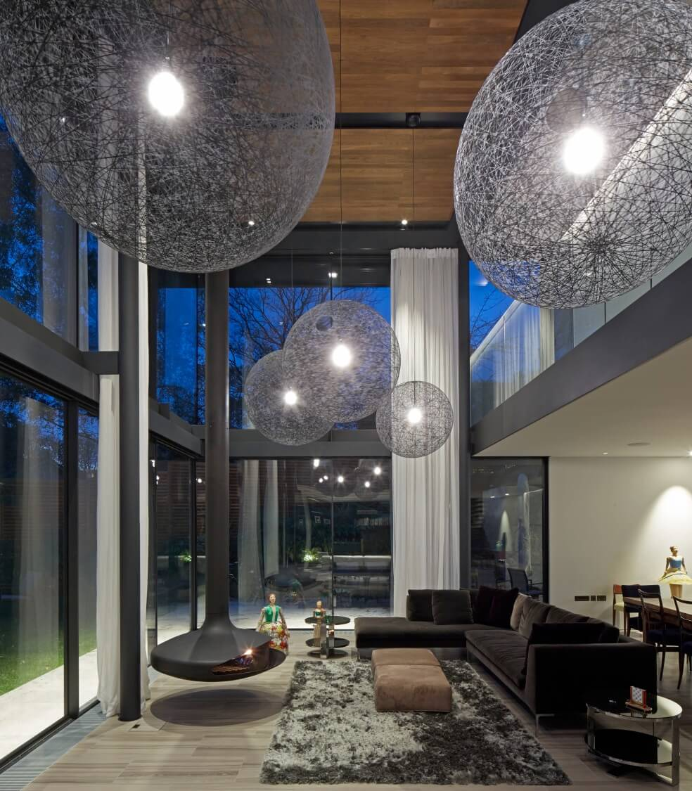 Here we see the same room at night, with the unique spherical chandeliers glowing overhead. The upper floor creates a loft-style space overlooking the living room.