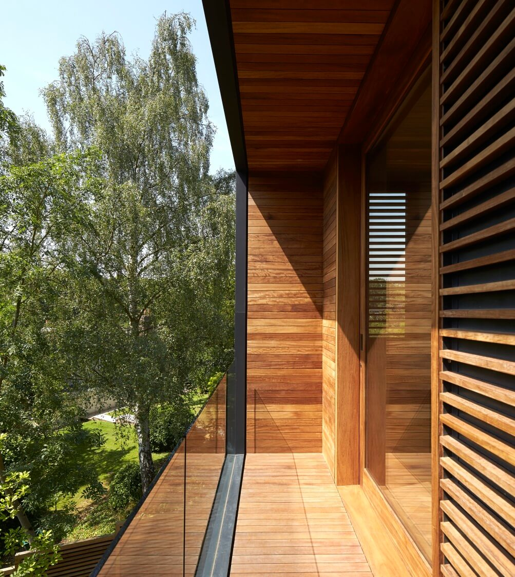 The balcony flaunts its rich natural wood framing, juxtaposed against frameless glass safety wall and the surrounding green environment.