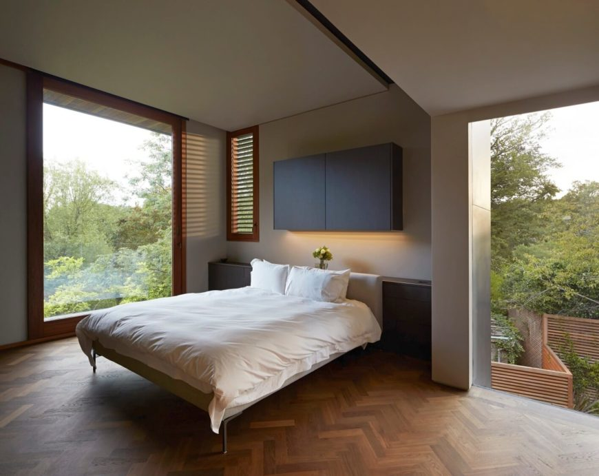 Contemporary primary bedroom features built-in storage and hardwood flooring with herringbone pattern.