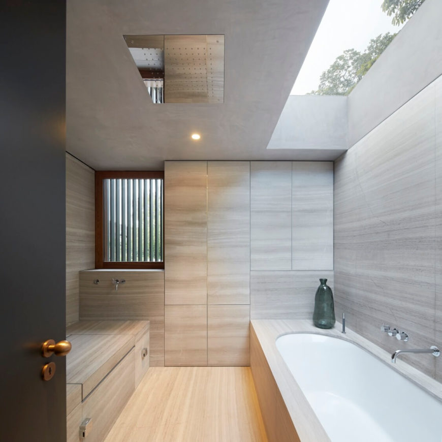 Cozy primary bathroom surrounded with light hardwood walls, flooring and built-in storage. Natural light streams through the skylight above the bathtub.