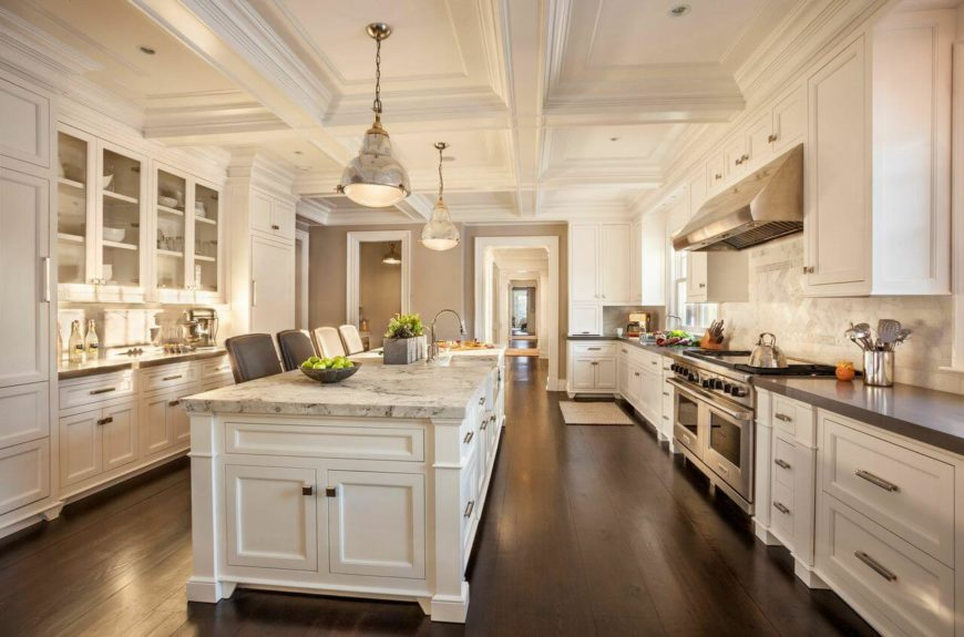 The cavernous kitchen is in a beautiful white that contrasts with the wide plank dark hardwood floors. Long chrome handles complement the stainless steel high-end appliances. The enormous marble-topped kitchen island has an eat-in bar for four.