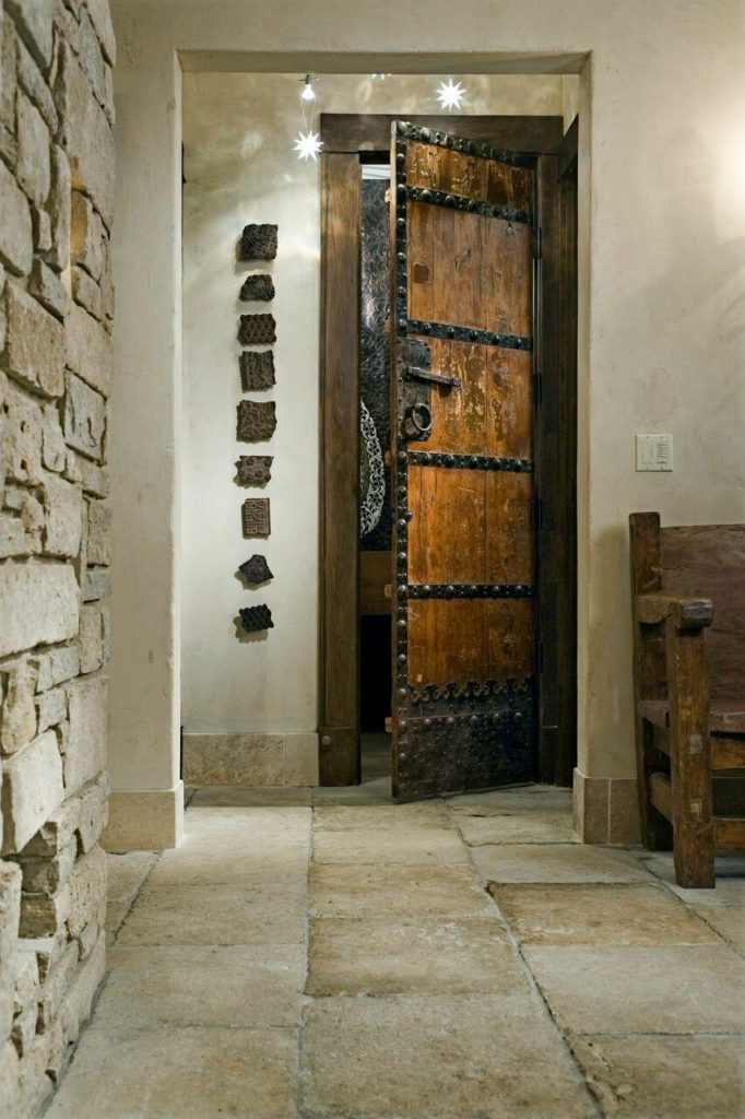 An iron and wooden door just past the bench leads to the main floor powder room. On the wall beside the bathroom door is a line of broken bits of heavily textured pottery.