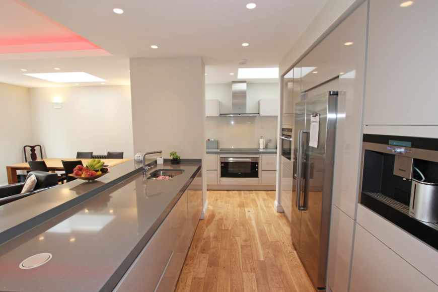 Sleek hardware-less cabinetry and modern appliances contrast with rich natural hardwood flooring.