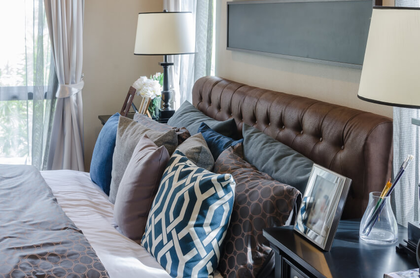 Complementary shades of blues, browns, and grays give this room a comfortable air and a classic feel. A plush leather headboard hosts a plethora of various throw pillows, creating a welcoming and comfortable space that is pleasing to the eye.