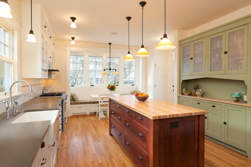 This honey wood floor is accented by the addition of a butcher's block countertop on the center island. The white walls keep the room feeling bigger while the built-in hutch in green adds visual interest to the room.