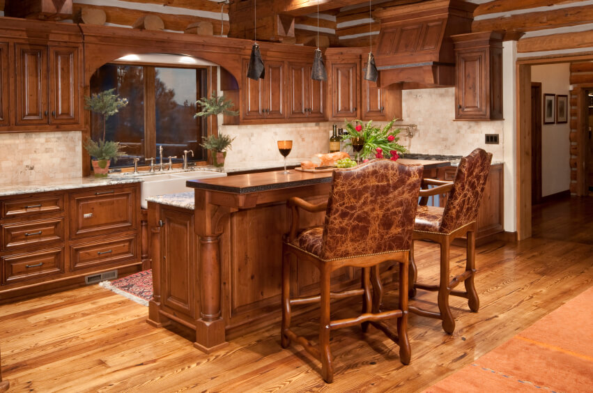 This light wood floor brightens up the dark wood of these cabinets while accenting the rustic tenor of the room. Ornate, leather upholstered bar stools stand at the two-tiered island for in-kitchen dining.