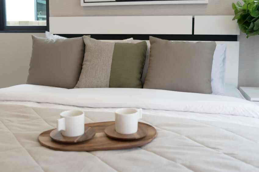 Symmetry is employed in a neutral space. Brown throw pillows flank a two toned accent pillow, while the entire lot is supported by traditional white bed pillows.