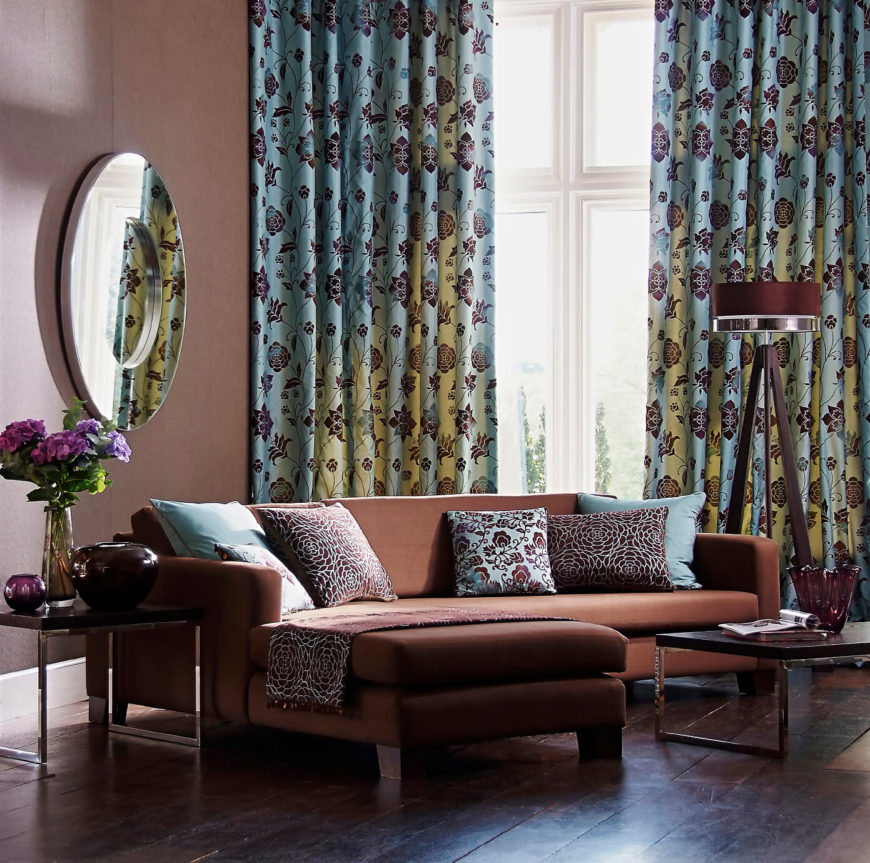 These blue floral curtains appear green where the light is shining through. Matching throw pillows on the solid dark brown sofa tie the design together.