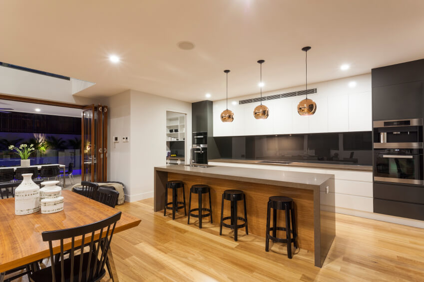 This beautiful, open kitchen boasts a high contrast look, with black and white walls and sleek lines. The lovely wood floors and copper pendent lights add color and warmth to the room.