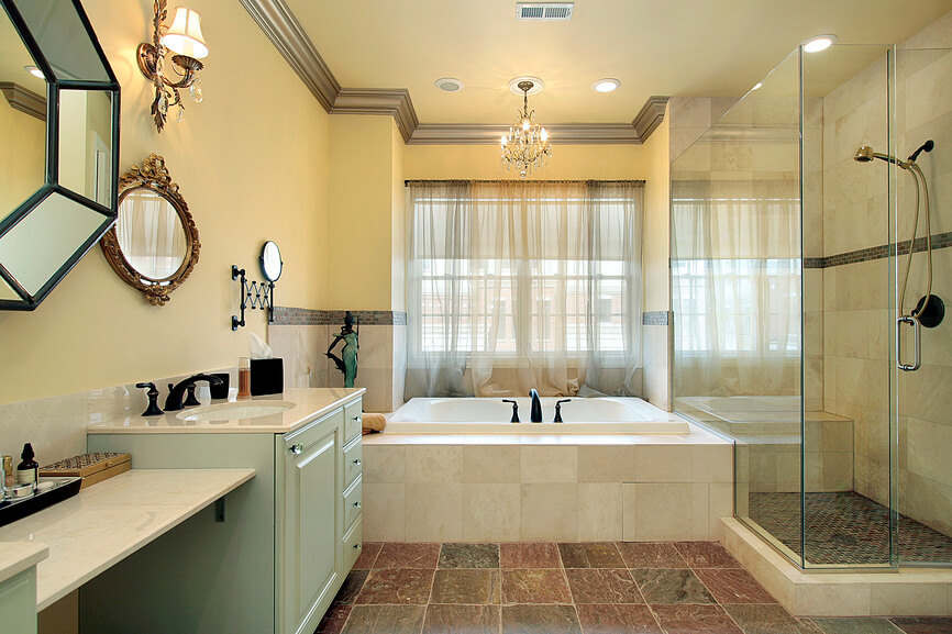 This primary bathroom features rich, earth-toned tile flooring, with dark shades of red and green, uniting a space filled with marble and soft yellow tones. All-glass shower enclosure at right hugs the large soaking tub, while a dual vanity at left sports soft green painted cabinetry.
