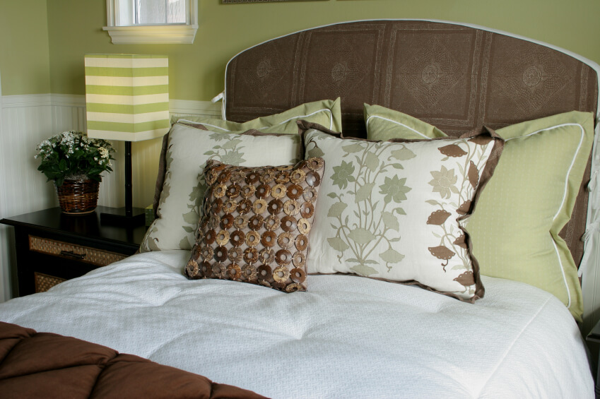 This wonderful arrangement is rich in color and texture. Sage pillows rest against a dark textured headboard, while light and patterned pillows support an unique chain pillow featuring various brown and beige stone or wood links. A striped lampshade coordinates perfectly and adds additional interest, while a lightly textured white comforter promises a soft and relaxing space.