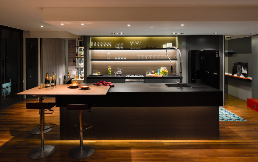The kitchen from the front is dominated by the backlit open shelving that acts as a display for the owner's varying glassware. Also of note is the paper composite countertop and the cantilevered eat-in bar.