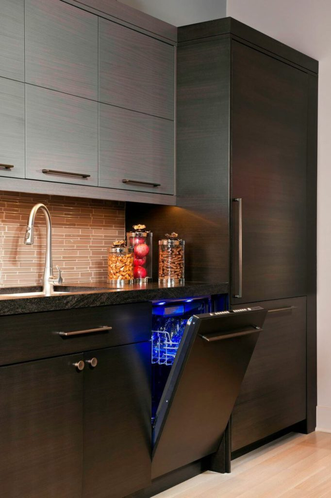 The other appliances, like the dishwasher, are hidden behind facades that match the lower cabinets. The inside of the dishwasher is lit with a brilliant blue light that gives it a futuristic cast.