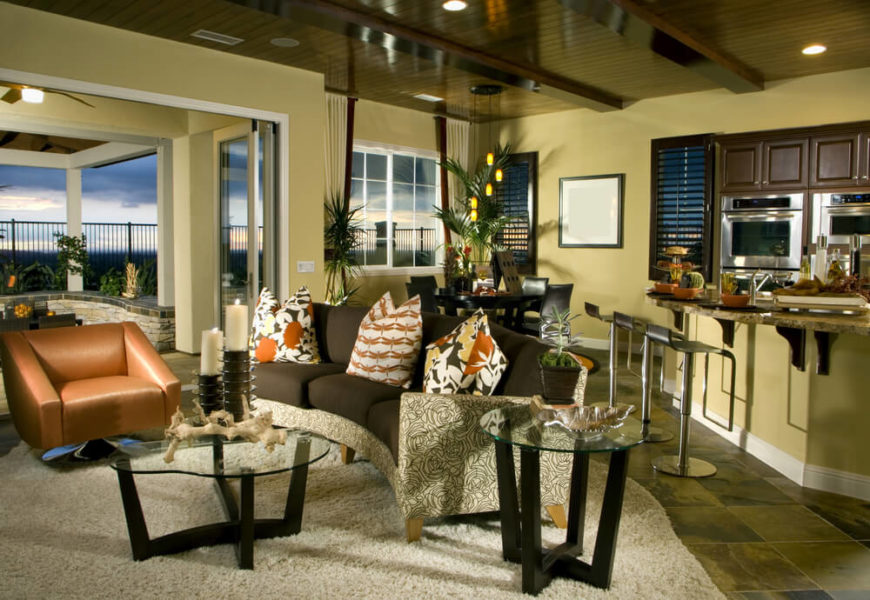 An open concept living room and kitchen with a dining room tucked into the rear corner. A single end table is in dark wood with a glass top, to match the curved coffee table. The table is used to display accents, like a small plant and a shell dish.