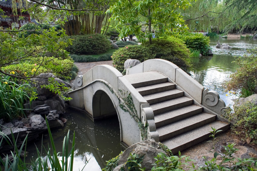The ornate swirls of stone along this arched stone bridge adds a whimsical element to this quiet, natural Japanese garden.