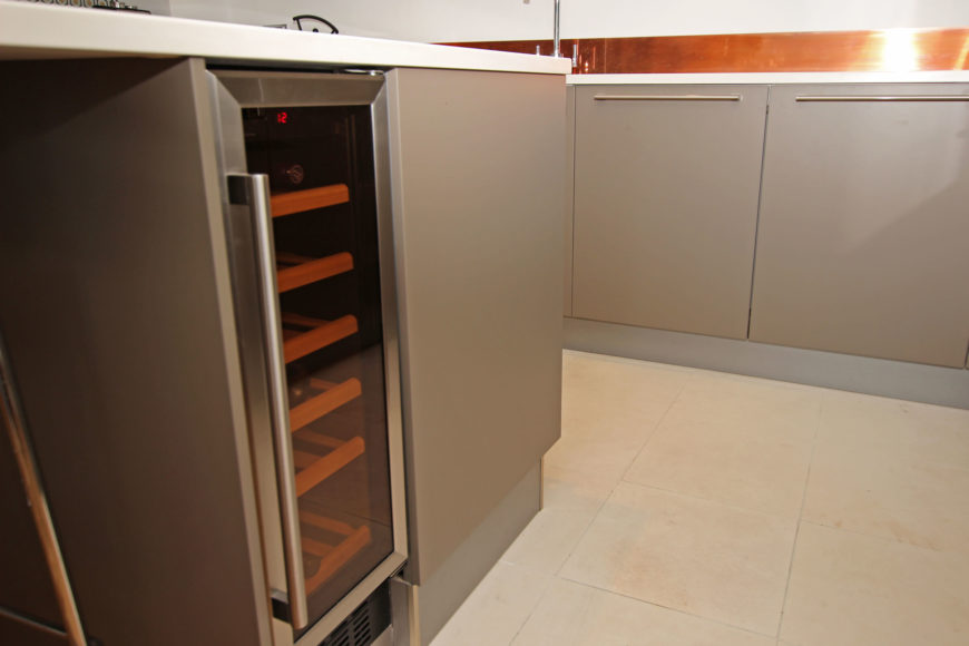 Here we see a close view of the beige tile flooring and island with built-in wine cooler.