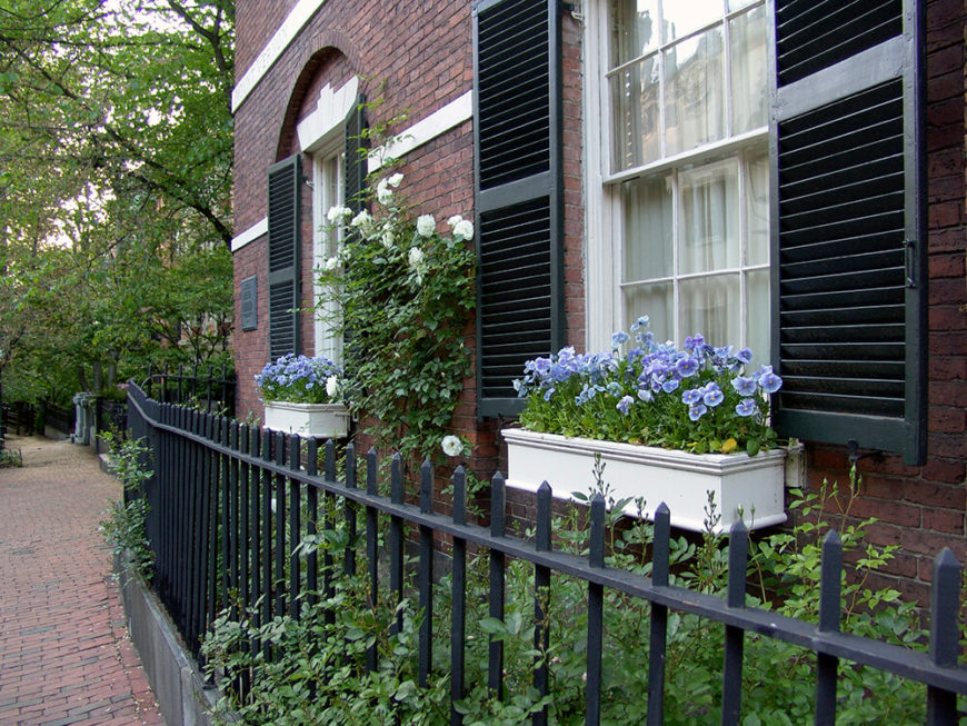 Two white window boxes add additional charm to an already quaint brick home with black shutters and a black wrought iron fence.
