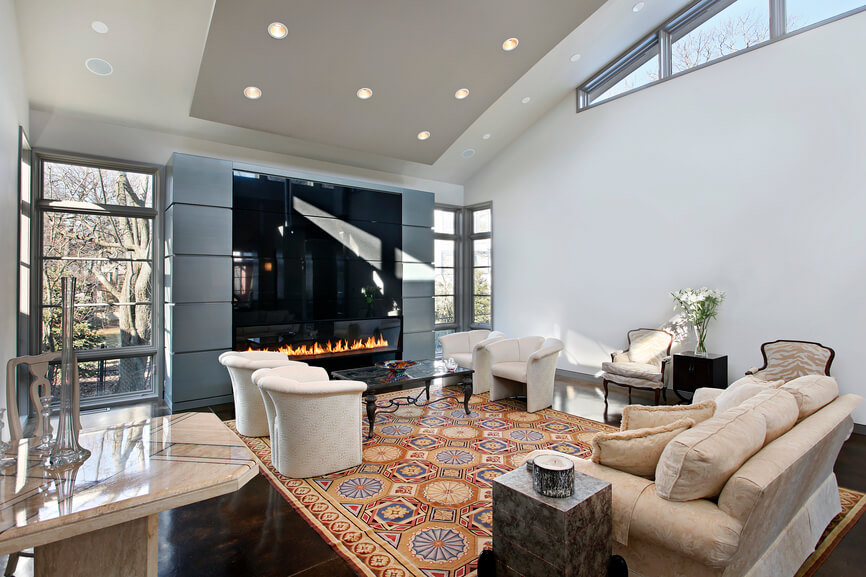 a cavernous white living room with a huge enclosed gas fireplace. This room's two separate seating areas have two end tables. While the grouping of four chairs near the fireplace have no need of table space, a cube table on one side of the sofa is a perfect place to set a candle. Between two beige and white zebra patterned chairs is another side table, this time in dark wood and topped with a glass vase full of flowers.