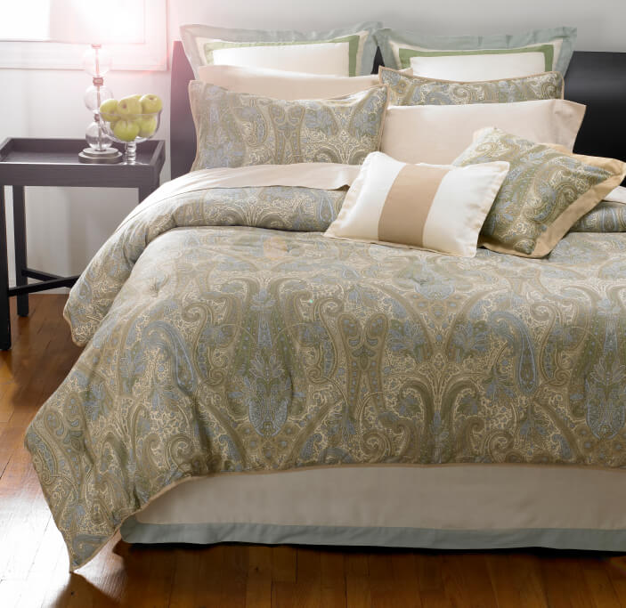 Lovely paisley linens in creams, sages, and blues are complemented by a variety of trimmed accent pillows in coordinating colors.