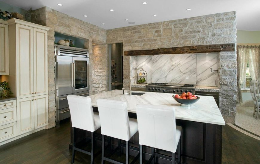 The white marble countertops match the marble backsplash behind the cooking range. Off to the right is the less formal dining room.