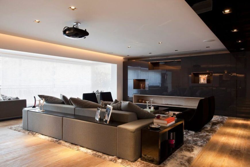 Another look at the living room. From this angle we can see a projector above the sofa. The screen, when retracted into the ceiling, eliminates the clutter of a television for a clean, minimalist space.