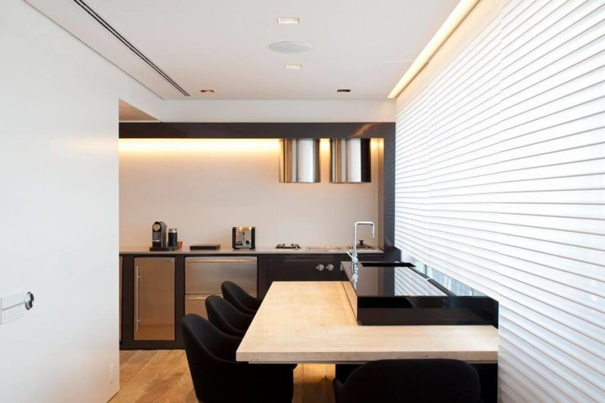 A close up on the kitchen, showing a two-tier eat-in bar and the simple, low-profile stainless steel appliances. Heavy white shades can be raised for more natural light from the expansive windows.