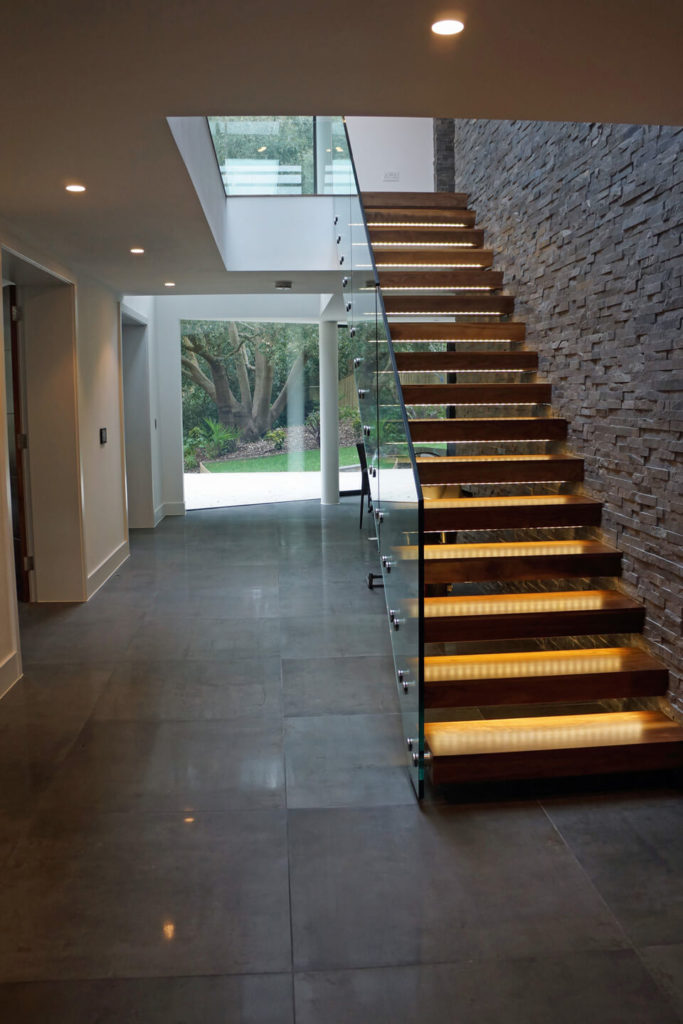 The staircase appears to float, courtesy of wall mounted hardwood steps with built-in lighting and an all-glass rail.