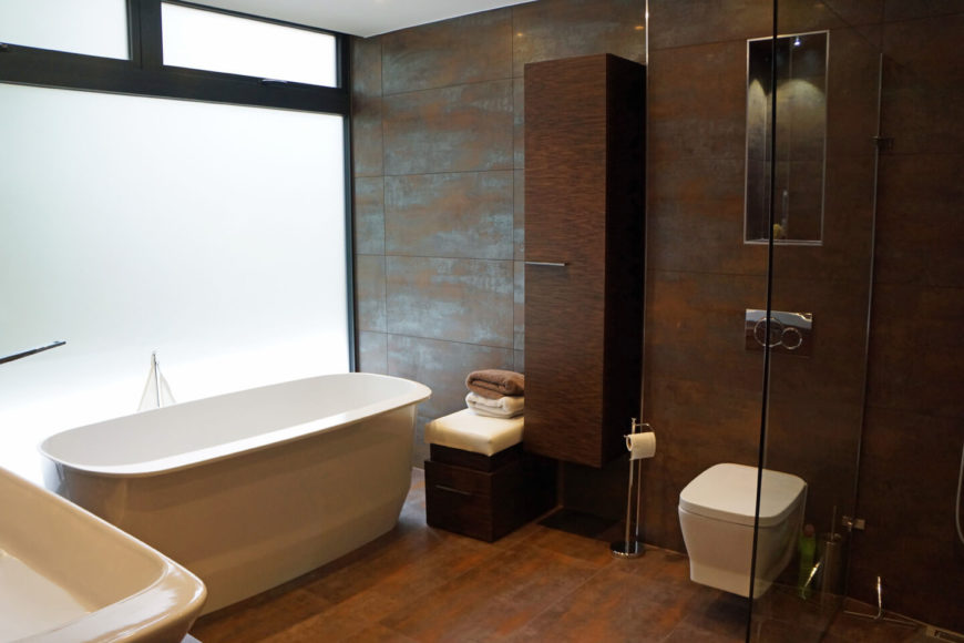 Contemporary primary bathroom accented by copper tones. It includes a freestanding tub near the frosted glass window and a toilet and shower area divided by tempered glass.
