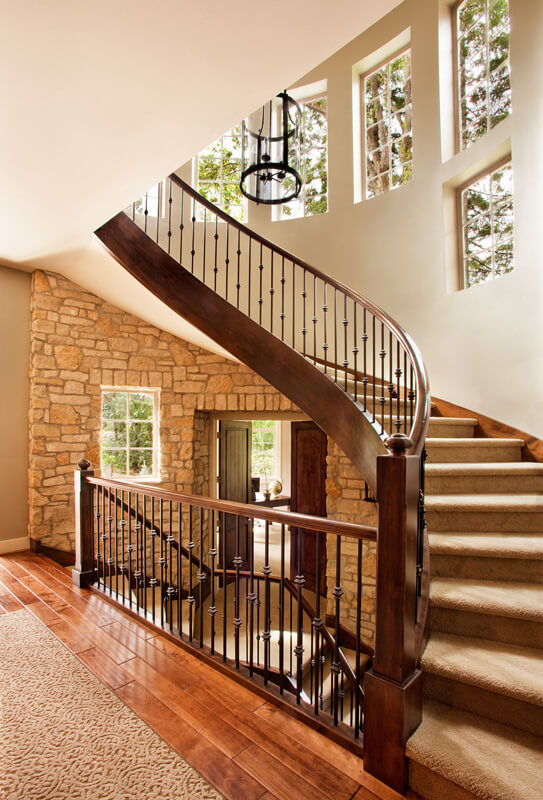 The grand, swirling staircase flaunts rich curved wood over the stone-wrapped foyer. A series of windows built into the curved wall highlight the immaculate vertical space.