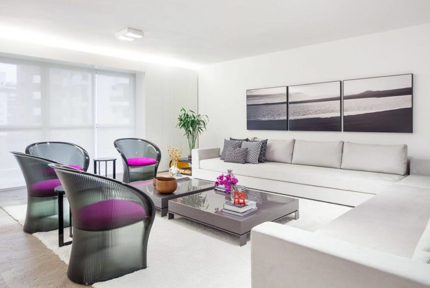 The formal living room has an enormous white sectional and four shapely, curved chairs in translucent gray. Shades can be pulled over the expansive windows for privacy without sacrificing light.