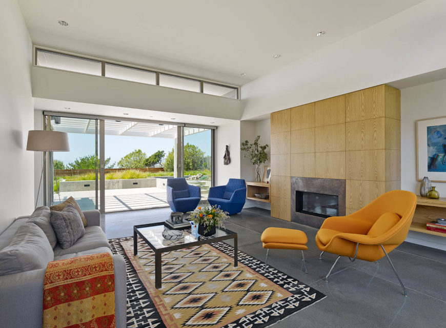 The living room is dominated by the large wood panel wrapped fireplace at right, with an array of multicolored contemporary furniture filling the space. The large scale sliding glass doors open to blur the line between indoors and out.