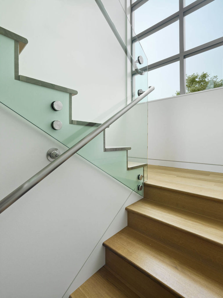 The rich hardwood stairs are lined with frameless glass railing, as seen beneath a large vertical array of windows.
