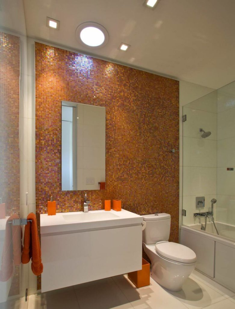Charming primary bathroom with a burst of orange. It is accented with multi-colored glass mosaic tiles wall where a frameless mirror is mounted.