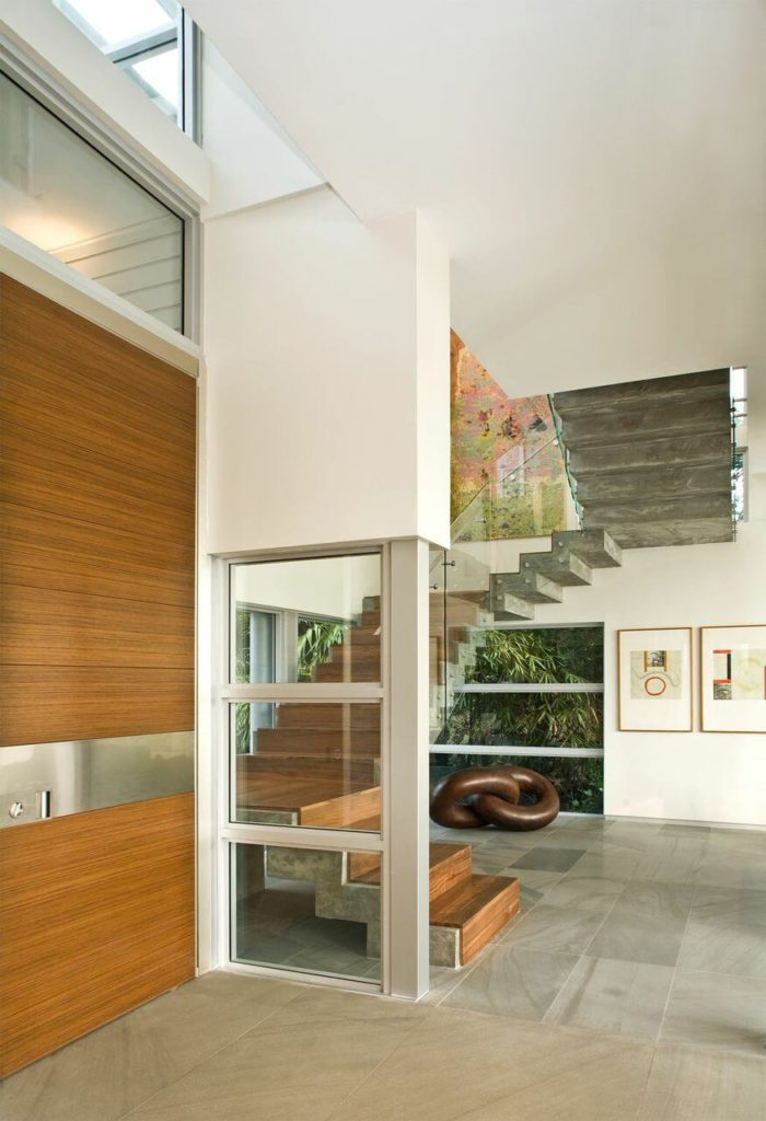 The simple foyer looks in on the wood and concrete staircase and modern art on the walls.