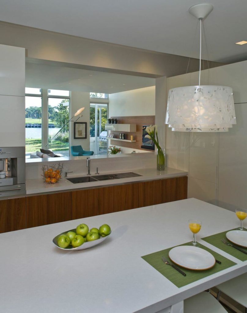 The kitchen has an eat-in island and glossy white countertops on warm wood cabinetry. A pass through looks out on the family room.