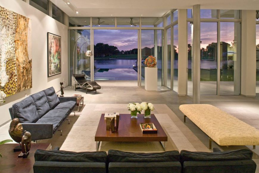 The rear of the living room has a sliding glass door that leads to the backyard patio and infinity pool that seems to disappear into the body of water beyond.