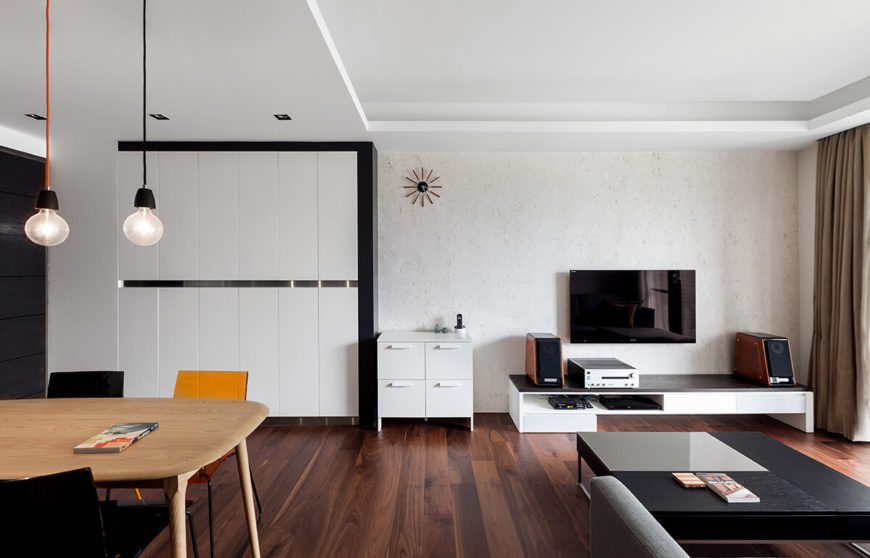 The broad open-plan space neatly combines two fully functional rooms, with subtly minimalist style informing the area. Entertainment wall in stone looms over a sleek media shelf, with black coffee table in foreground.