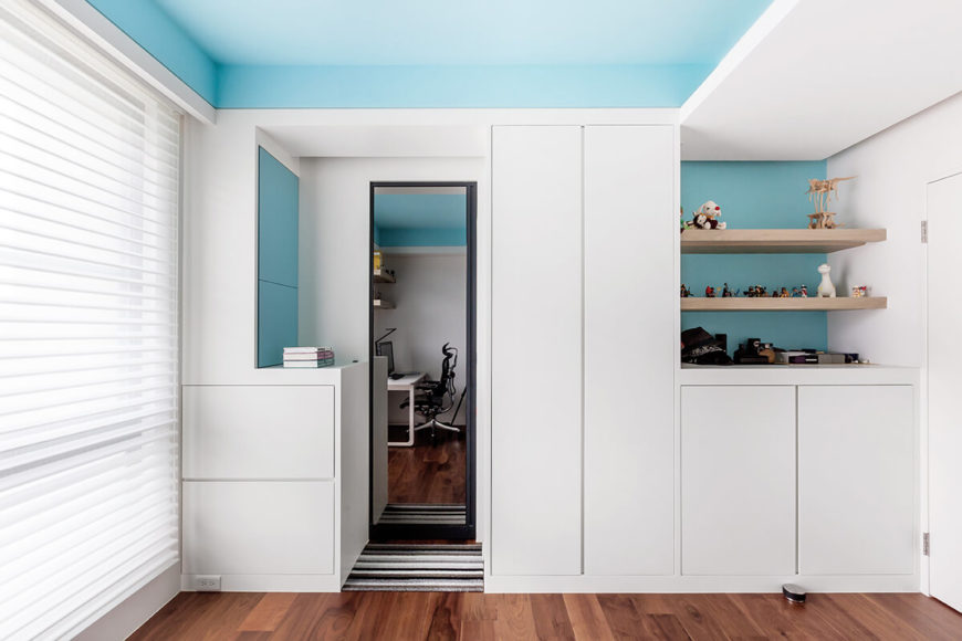 The sky blue tones mesh with white walls for a sunny day appearance, over the rich hardwood flooring.
