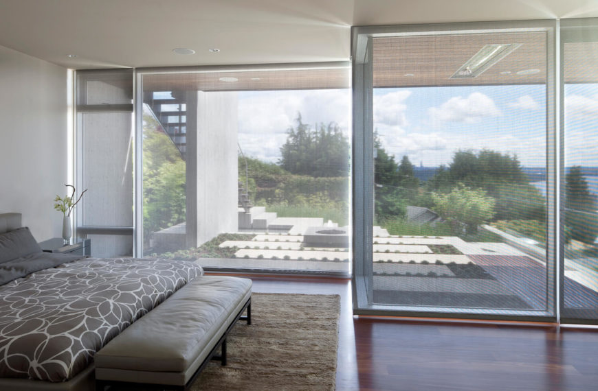 Gray primary bedroom surrounded with glass walls covered by blinds. It has a tufted bed with floral pattern bedding and an upholstered leather bench on its end over a shaggy rug.