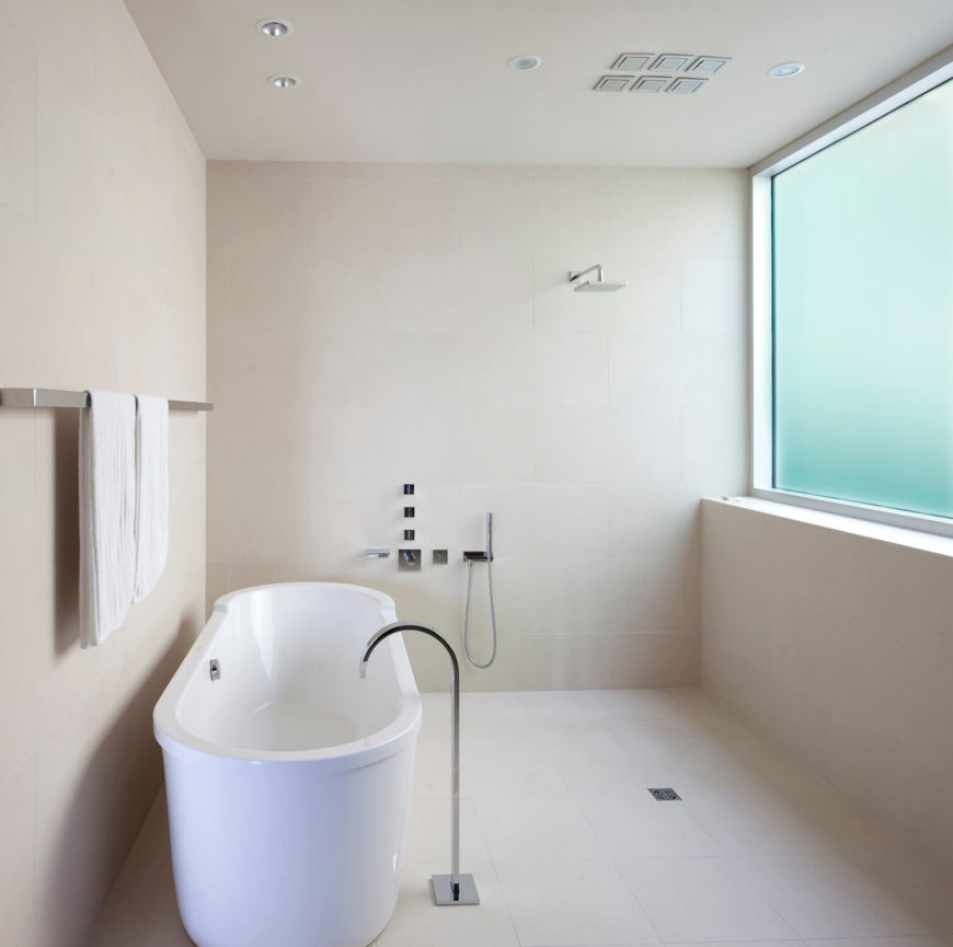 Bathroom features sleek tiling floor to ceiling, surrounding a large white pedestal tub with free standing faucet.