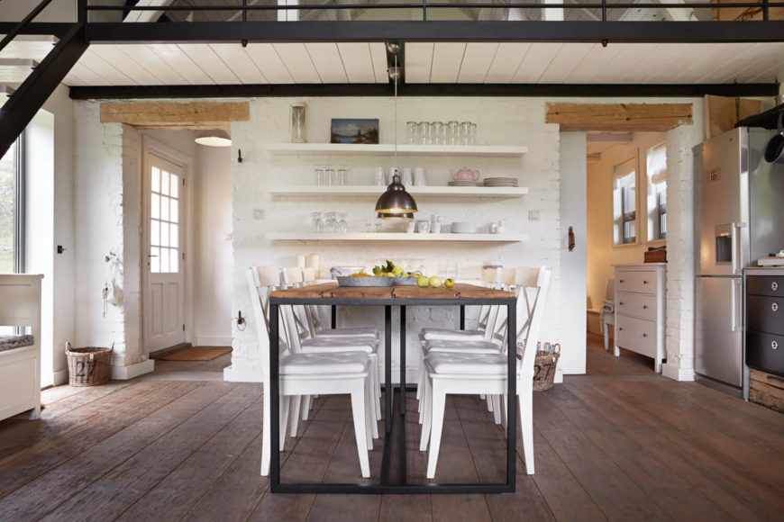 Beneath the catwalk-like edge of the loft, the dining area stands centered around a wrought iron and natural wood table. White shelving floating on white brick wall stands between a pair of doorways with exposed wood beam lintels.